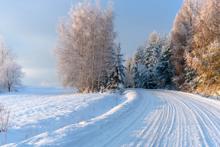 Winter landscape - snow covered mountain road on a cold and sunny morning Standard-Bild