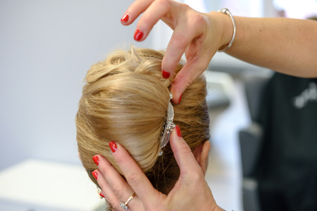 Professional services in the hairdressing salon  - a young woman with blonde hair has made hairstyles for a wedding party. Stock Photo