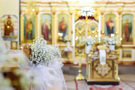 Decoration of wedding flowers against the background of a beautifully blurred orthodox church interior