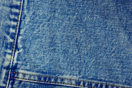 Textured vintage background - blue jeans textile denim with seam of fashion design in close-up (high details). Stock Photo