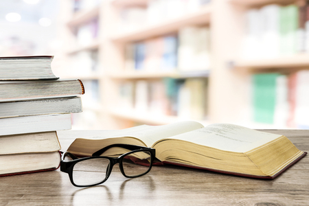 Concept image of education and learning - stocks of books next to open book and eyeglasses on a desk in the library.
