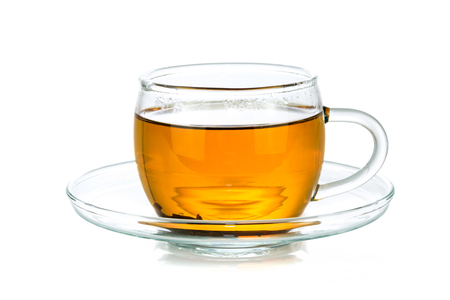 Transparent glass cup of tea isolated on a white background in close-up
