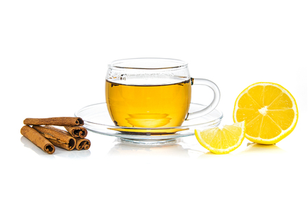 Concept image of a healing and warming drink - hot cup of tea with cinnamon and lemon isolated on a white background.