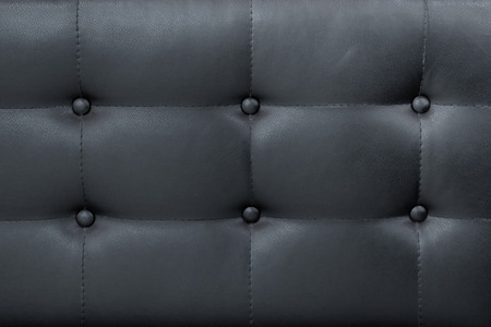 Luxury black leather sofa with buttons background.