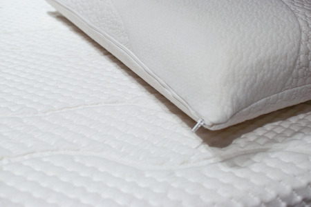 Modern and healthy bed with white mattress and pillow in close-up.