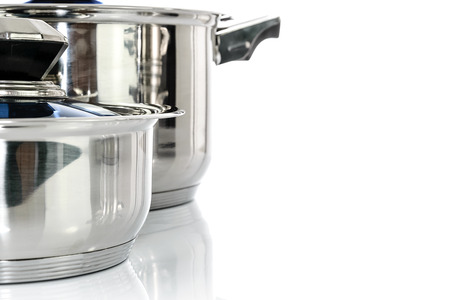 Culinary background - group of premium stainless steel pots and pans isolated on a white background with copy place.