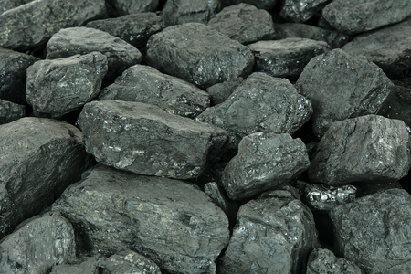 Concept of energy fuel - black coal in close-up as a texture or background