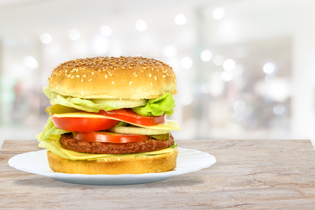 Composite image of tasty hamburger, beef burger in close-up on a plate in the restaurant.