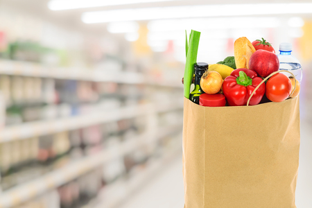 Grocery shopping concept image - Eco friendly paper shopping bag filled with various food products on  blurred supermarket background.