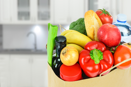 Grocery shopping concept image - Eco friendly paper shopping bag filled with various food products in the kitchen. Stock Photo