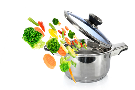 Healthy cooking concept image - mix vegetables falls into a stainless steel pot isolated on a white background.