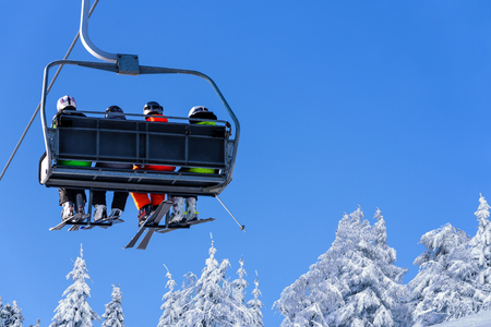 Skiers on a ski lift in the mountain on the background of a clear blue sky with copy space.