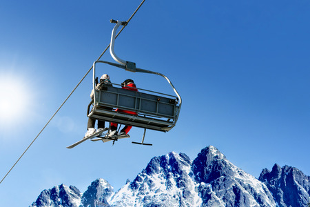 Skiers on a ski lift in high mountains on the background of a clear blue sky with copy space.
