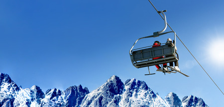 Composite image of skiers on a ski lift in high mountains on the background of a clear blue sky with large copy space.