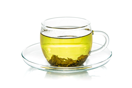 Transparent glass cup of natural green tea isolated on a white background in close-up  Stock Photo