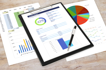 Composite image of business analytics in the office - pen and clipboard with printouts of digital data and charts on the desk.