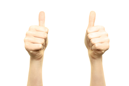 Woman is holding two thumbs up into the air on a white background