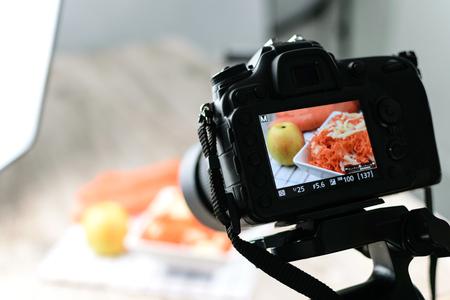 Imagen conceptual: vista posterior de la cámara réflex digital que hace una fotografía de alimentos en el estudio fotográfico