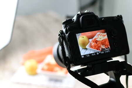 Concept image  -  rear view of DSLR camera making a food photography in the photo studio