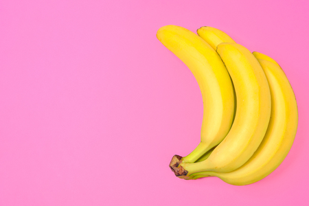 Funny concept image - bunch of bananas isolated on a pink background in top view (copy space)