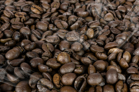 Coffee production background - many hot roasted brown beans and smoke in close-up as a texture  (high details).