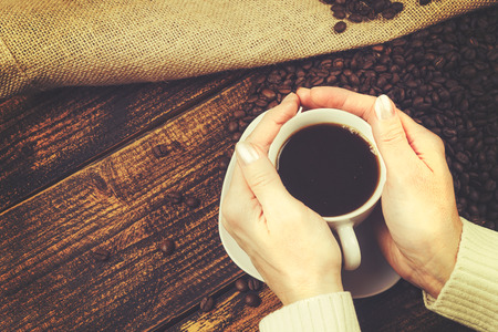 Concept of coffee tasting in a rustic style - the woman holds a cup of coffee in her hands on a wooden table with spilled beans from a burlap sack (vintage effect). Stock Photo