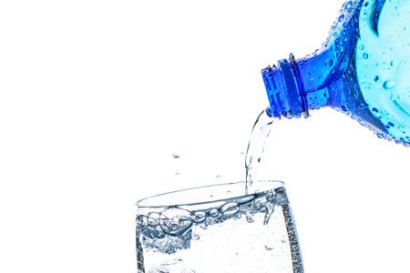 Fresh mineral water is poured into a glass with a splash on a white background in close-up (copy space for add text)