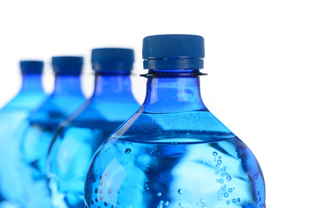 Fresh mineral water concept - cool bottles of mineral water in a row on a white background in close-up. Stock Photo
