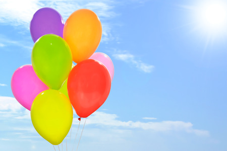 Party decoration concept - mix of colorful balloons on a blue sky background with copy space (mixed).