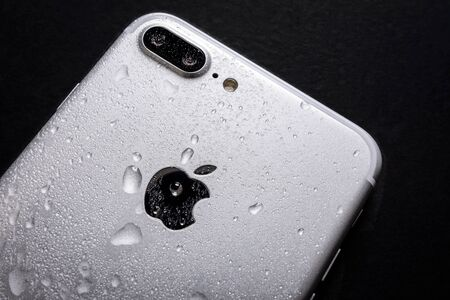 Krynica, Poland, May 02, 2018:  Close up of the Apple iPhone 7 Plus with water drops on a back side - smartphone water resistance test. 에디토리얼