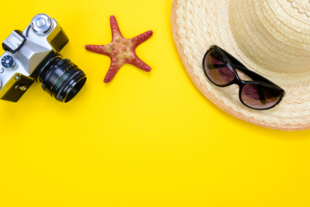 Summer holidays and vacation concept - sunglasses, starfish and a beach straw hat next to retro slr camera on a yellow background with copy space.