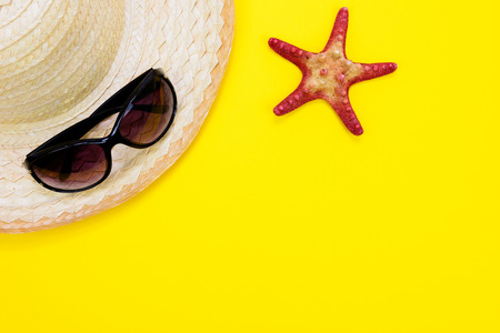 Summer holidays and vacation concept - sunglasses, starfish and a a retro beach straw on a yellow background with copy space. Stock Photo