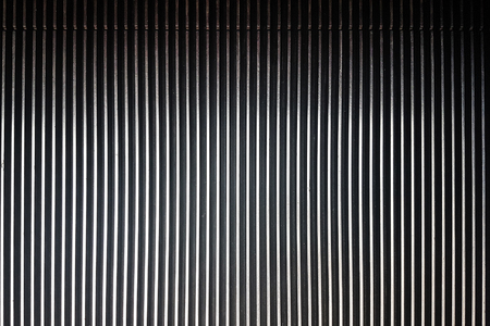 Textured background of striped pattern of a metal escalator in close-up
