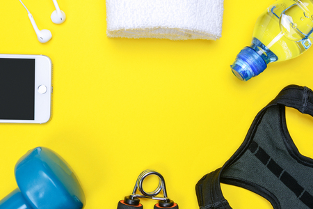 Fitness activity concept - flat lay of some personal sport accessories for woman on a yellow background with copy space. Stock Photo