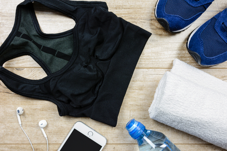 Fitness activity concept - flat lay of some personal sport accessories for woman on a wooden background.