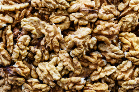 Background of shelled dried walnuts in close-up (high details)