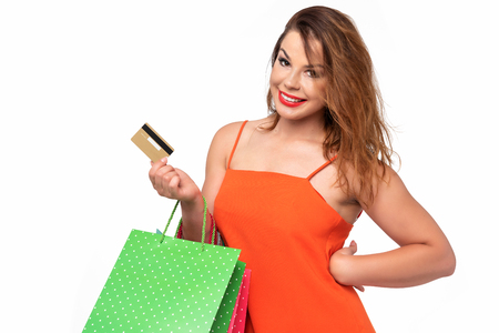 Attractive and young woman in an orange dress holds a credit card in her hand and enjoys shopping