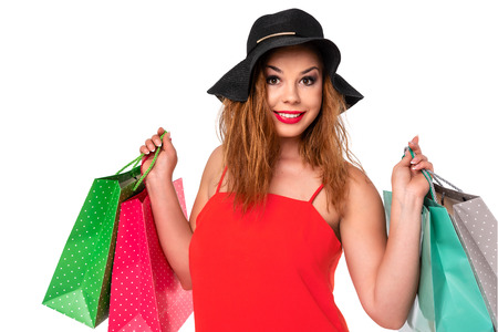 Attractive and young woman in a red dress holds bags in her hands and enjoys shopping. Stock Photo