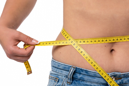 Healthy lifestyle concept - woman in blue jeans measures her waistline with a measuring tape in close-up