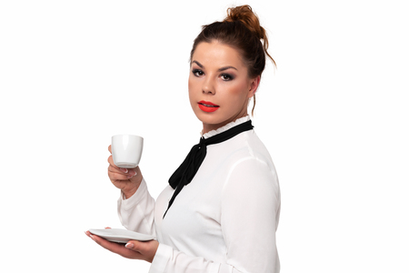 Beautiful businesswoman holding a cup of coffee in her hands and enjoying its flavor on a white bakcground