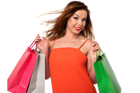 Attractive and young woman in an orange dress holds bags in her hands and enjoys shopping.