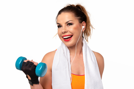 Fitness activity concept - beautiful young woman in sportswear with towel, earphones and dumbbells making workout.
