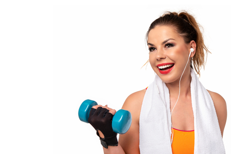 Fitness activity concept - beautiful young woman in sportswear with towel, earphones and dumbbells making workout (copy space) Stock Photo