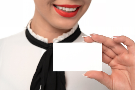 Young business woman with perfect smile and fingernails holds blank business card in close-up on a white background. Stock Photo