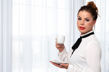 Beautiful and elegant woman holding a cup of coffee in her hands and enjoying its flavor on a background of luxury interior (copy space). Stock Photo