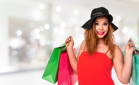 Attractive and young woman in a red dress holds bags in her hands and enjoys shopping on a blurred background of luxury mall (copy space).