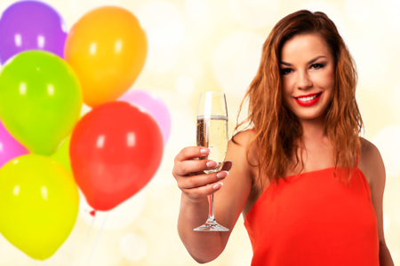 Celebration event concept - young and attractive woman in a red dress with perfect fingernails holds a glass of champagne or wine and smiling on a party decoration background (mixed).