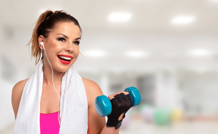 Fitness activity banner - beautiful young woman in sportswear with towel, earphones and dumbbells making workout on a blurred background of a gym (copy space)