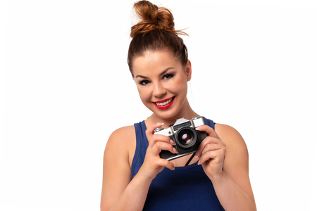 Amateur photographer concept - beautiful and attractive woman holding a retro SLR camera and smiling isolated on a white background.