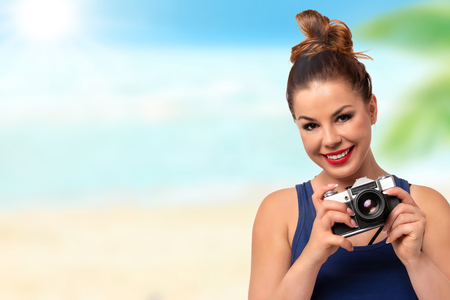 Vacation photographer concept - beautiful and attractive woman holding a retro SLR camera and smiling on blurred background of a tropical beach (copy space).